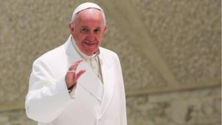 Pope Francis in white robes, waving
