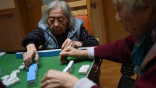 Elderly people playing dominoes in a Chinese nursing home