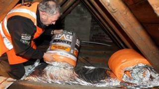 Man fitting loft insulation