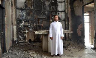 Father Anthony inside the fire-damaged church