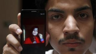 Hassan Khan shows the picture of his wife Zeenat Rafiq, who was burned alive, allegedly by her mother, on a mobile phone at his home in Lahore, Pakistan Wednesday, June 8, 2016.