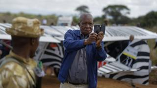 A spectator takes a selfie in front of a non-vintage support aircraft that landed in Nairobi National Park in Kenya, Sunday 27 November 2016