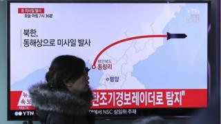 """A visitor walks by the TV screen showing a news program reporting about North Korea""""s missile firing, at Seoul Train Station in Seoul, South Korea, Monday, March 6, 2017"""