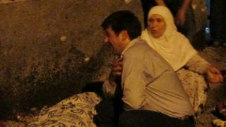 A man and woman mourn next to a body of one the victims in Gaziantep