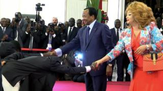"""This video grab image created on February 8, 2017 shows Cameroonian national football team players perform a """"deep bow"""" to President Paul Biya (L) and his wife Chantal Biya in Yaounde, following their 2-1 victory over Egypt in the finals of the 2017 Africa Cup of Nations in Libreville, Gabon."""