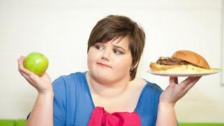 Woman choosing between apple and burger
