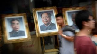 People walk past a portrait of Mao Zedong