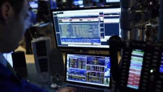 A trader looking at computer screen at New York Stock Exchange