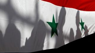 The shadows of people on a Syrian national flag (21 September 2016)