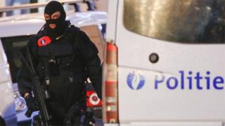 A Belgian special forces police officer patrols a street during a police raid in central Brussels (image from 20 December)