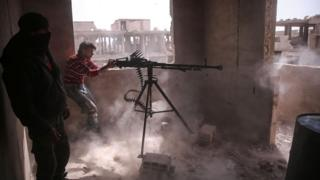 Rebel fighter from the Faylaq al-Rahman faction fires a machine-gun at government positions in Jobar, Damascus (19 March 2017)