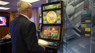 A customer plays a slot machine at a William Hill