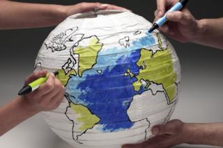 Two people colouring in paper globe