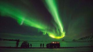 Tourists photograph the Northern Lights in Iceland