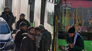 Men react as they stand outside buses evacuating people from a rebel-held sector of eastern Aleppo