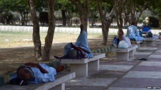 Pakistani men rest in the shade of trees