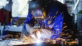 Worker welding metal in workshop with sparks