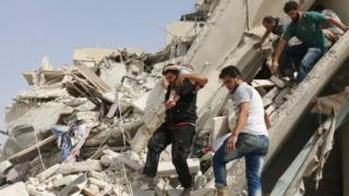 Syrian men remove a baby from the rubble of a destroyed building following a reported air strike in the Qatarji neighbourhood of the northern city of Aleppo (21 September 2016)