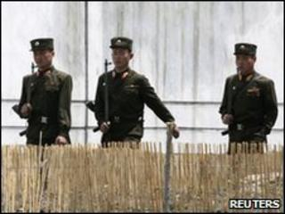 North Korean soldiers patrol the banks of the Yalu River, opposite the Chinese border city of Dandong, 25 May 2010