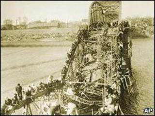 Civilians crawl over a shattered bridge in Pyongyan to escape the advance of Chinese troops