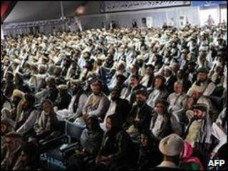 """Delegates look on as Afghan President Hamid Karzai delivers a speech at the """"peace jirga"""""""