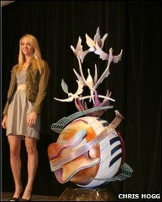 Artist Lauren Voiers and a model of her John Lennon Peace Monument