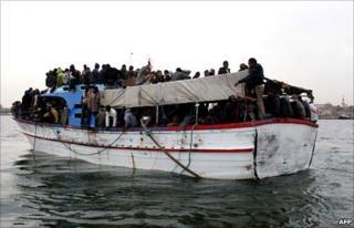 Migrants on a boat in Tripoli's port