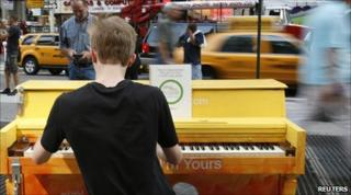 A tourist plays a street piano in New York's Times Square