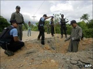 Thai bomb squad members inspect the crater at the site of a roadside bomb