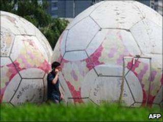A man walks past giant footballs in Beijing
