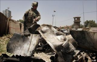 Iraqi soldier stands over wreckage at the site of the bombing