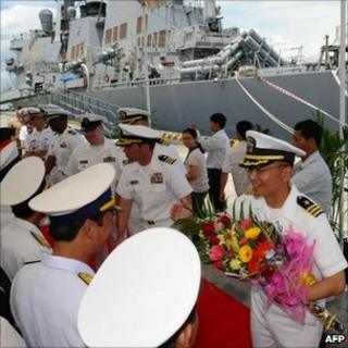 US commander Jeffrey Kim (R) and his crew are greeted by Vietnamese naval officers at Tien Sa port in the central coastal city of Danang