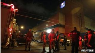 Soldiers and police stand outside the offices of Televisa in Monterrey