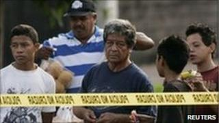Salvadorans looking at a crime scene on 21 June 2010