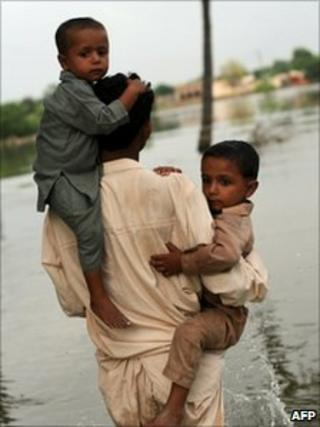 Pakistani villager carries two boys as he walks through water in Baseera