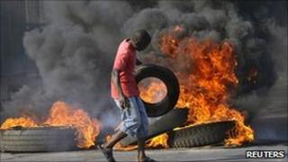 A demonstrator throws a tyre on a burning barricade during riots in Maputo