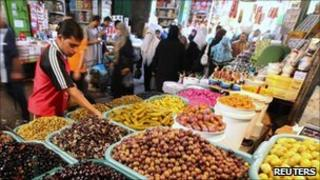 A man buys olives at a market in Gaza City, August 2010