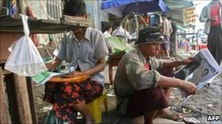 A man reads a newspaper in Rangoon. Photo: August 2010