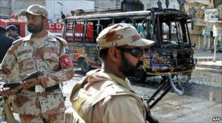 Pakistani soldiers in Karachi patrol the area around a minibus torched by protesters, following the murder of Imran Farooq