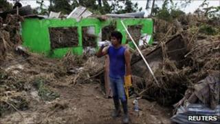 A resident drinks water next to his damaged house after Hurricane Karl hit in Cascajal near Veracruz