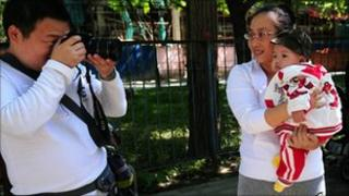 A father takes a photograph of his baby girl being held in her mother's arms at a park in Beijing