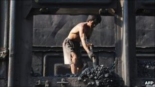 A Chinese miner unloads coal from a train in Hefei, in eastern China's Anhui province
