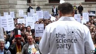 Protesters including scientists gather outside the Treasury in London to protest Government cuts to science (PA)