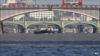 A tug boat plies its trade along the River Thames, with Lambeth Bridge in foreground, and Westminster Bridge