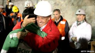 In this handout from the Chilean government, Ariel Ticona, the 32nd miner to be rescued, is hugged by Chile's president Sebastian Pinera on October 13, 2010 at the San Jose mine near Copiapo, Chile.