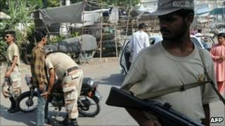 Pakistani paramilitary soldier frisks a motorcyclist in Karachi