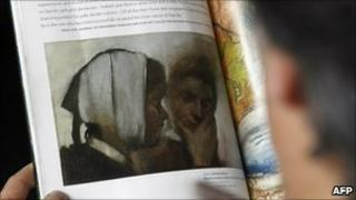 Person reads catalogue featuring the painting