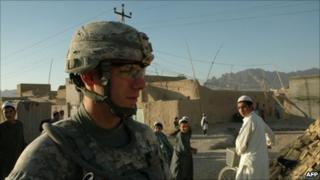 Boys watch US soldier on patrol in Kandahar