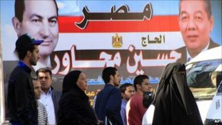 People in Cairo walk in front of election poster featuring President Hosni Mubarak (left) and a ruling NDP candidate
