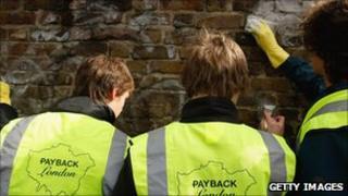 Youths clean graffiti off wall